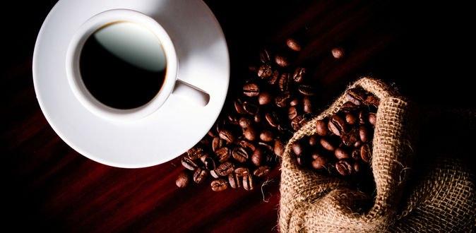 Обои Белая чашка с кофе на блюдце рядом с мешочком с зернами кофе