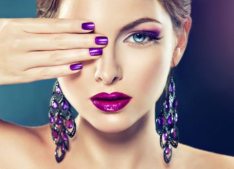 Обои Модель с огромными фиолетовыми сережками закрыла правый глаз рукой