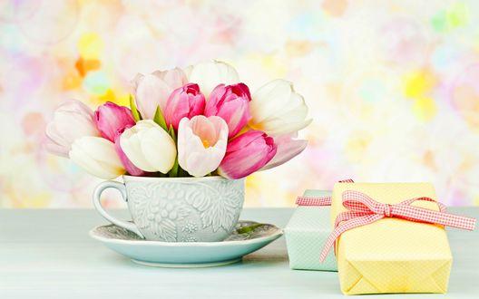 Обои Подарки лежат на столе возле кружки с букетом тюльпанов