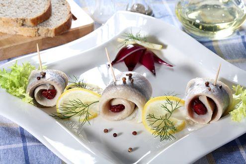 Обои Белая тарелка с селедкой на шпажках, лимон и зелень