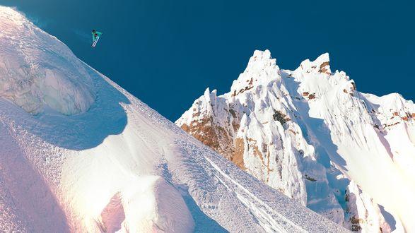 Обои Сноубордист выполняет трюк над снежной вершиной горы