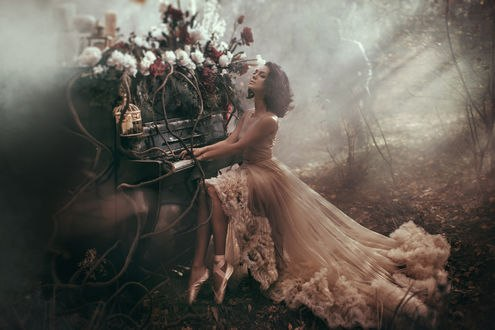 Обои Девушка - балерина положила руки на пианино, из которого растут цветы и висит клетка с птицей на фоне пробивающихся солнечных лучей в лесу, фотограф Валерия Мытник