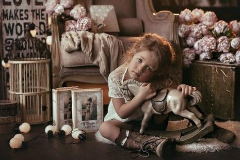 Обои Грустная маленькая девочка сидит на меховом коврике, обняв деревянную лошадку, фотограф Валерия Мытник