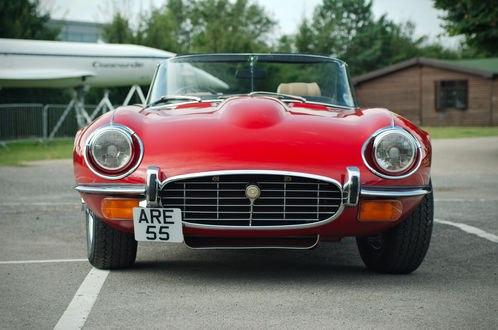 Обои Красное спортивное авто стоит у гаража