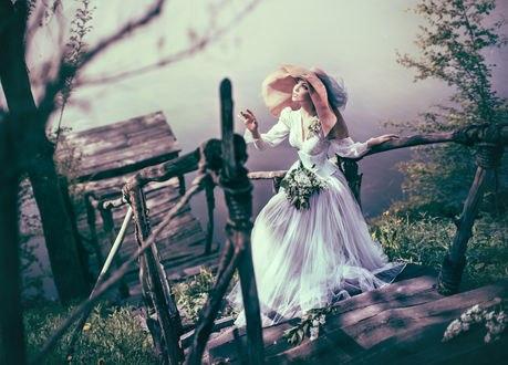 Обои Красивая девушка в белом длинном платье цветами, в шляпе стоит на ступенях деревянной лестницы, ведущей на мост к воде, фотограф Валерия Мытник