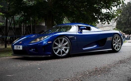 Обои Синий спорт-кар припаркован возле домов