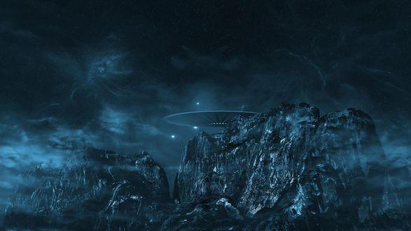 Обои Над скалами висит НЛО на фоне темного неба