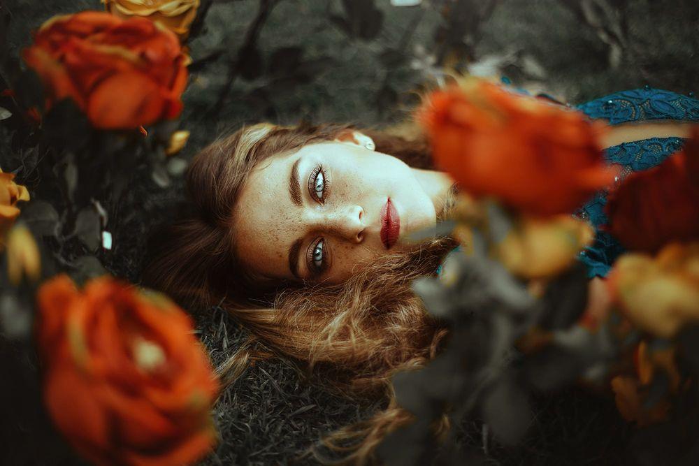 Обои для рабочего стола Девушка с веснушками на лице лежит среди цветов, фотограф Ronny Garcia