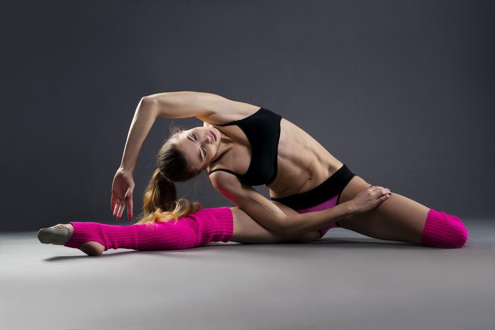 Обои для рабочего стола Спортивная девушка в розовых гетрах занимается йогой на сером фоне