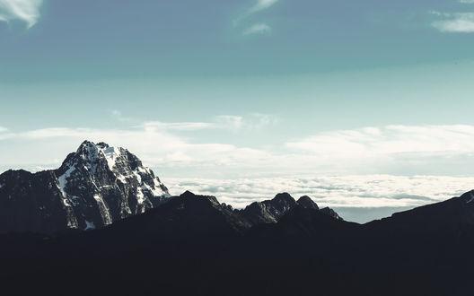 Обои Темные горные вершины над облаками на фоне неба