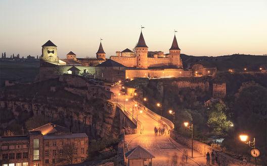 Обои Освещенная фонарями дорога к замку в горах