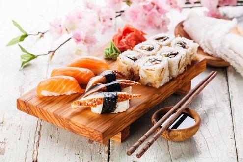 Обои Японская кухня: суши и роллы, маринованный имбирь и васаби на деревянной подставке, рядом полочки для еды и ветка сакуры