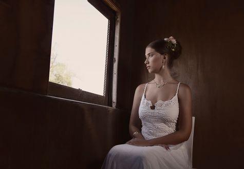 Обои Красивая, грустная девушка, с цветами на волосах, с украшениями, в белом платье, сидит у окна и смотрит вдаль