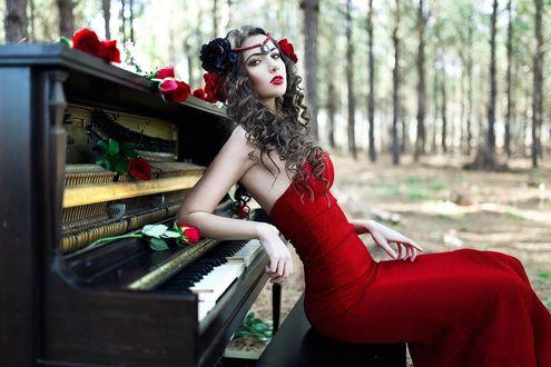 Обои Девушка в красном платье, с украшениями на волосах, сидит спиной к пианино, опираясь на него