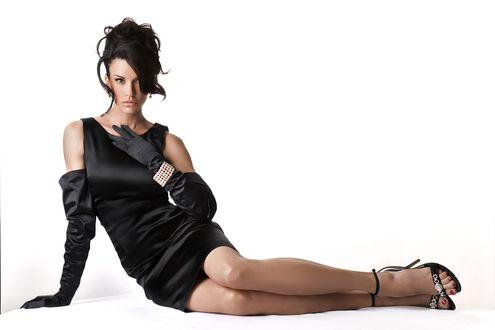 Обои Американская актриса и модель Дженис Дикинсон / Janice Dickinson в черной одежде, в длинных черных перчатках, с украшениями, сидит на полу на белом фоне