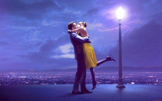 Обои Влюбленные обнимаются и целуются на крыше здания под фонарем, на фоне города и ночного неба
