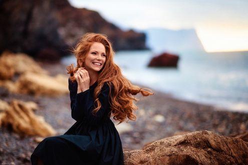 Обои Модель Оксана Бутовская, с рыжими волосами, сидит на камне, на размытом фоне морского побережья, Фотограф Лена Смирнова