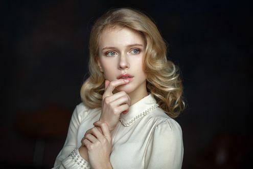 Обои Модель Алиса со светлыми волосами, в белой одежде, положив палец на губу, смотрит вдаль, на размытом темном фоне. Фотограф Настасья Паршина