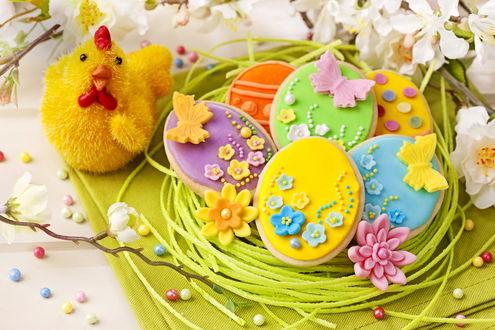 Обои На салфетке лежат сладости, веточки с белыми цветами и стоит желтая курочка курочка