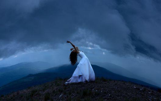 Обои Девушка в белом длинном платье, стоит на вершине горы, прогнувшись назад и подняв руки вверх, на фоне облачного неба