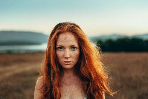 Обои Модель Оксана Бутовская с рыжими волосам, с веснушками, с оголенными плечами, на размытом фоне природы