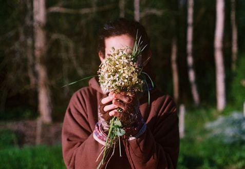 Обои Парень прикрыл лицо букетиком цветов, by Agustín Galeano