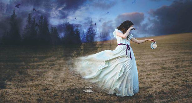 Обои Девушка в белом платье с будильником в руке стоит в поле
