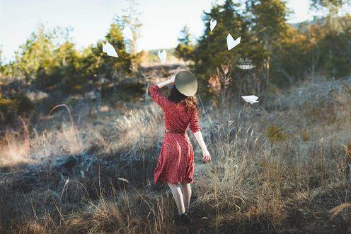Обои Девушка в красном платье стоит перед летающими бумажными самолетиками