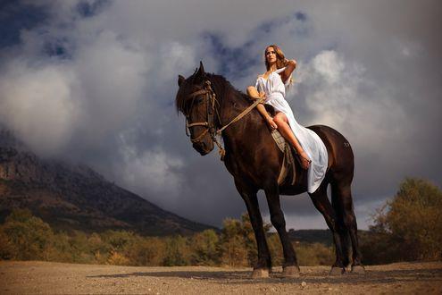Обои Девушка в белом платье, верхом на коне, на фоне природы, смотрит вдаль. Фотограф Роман Гутиков