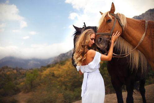 Обои Девушка, положив голову на морду лошади, гладит ее рукой, на фоне горного пейзажа. Фотограф Роман Гутиков