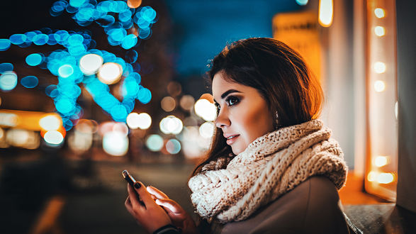 Обои Красивая девушка в руке с мобильным телефоном, смотрит в сторону, на фоне ночных огней города. Фотограф Антон Харисов