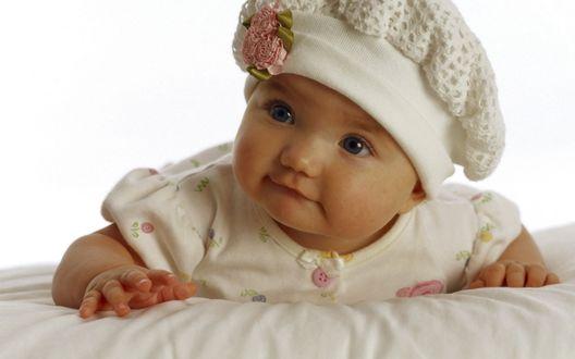 Обои Милая маленькая девочка, в вязанной шапочке с цветами, на белом фоне