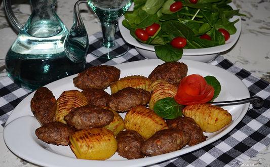 Обои Блюдо с небольшими котлетками с запеченной по - деревенски картошкой, украшенное розой из свеклы и листиками базилика, рядом блюдо с листьями салата корн и помидорками черри, композицию завершает красивый кувшин с фужером