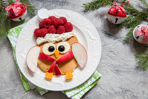 Обои Смешная картинка, сложенная из кусочков яблок, банана, оливок и апельсина, малины и сливок, лежащих на блинчике