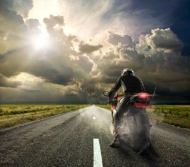 Обои Парень в шлеме на мотоцикле, на пустой дороге, на фоне неба, облаков и солнца