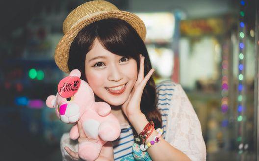 Обои Восточная девушка в шляпке держит в руке игрушку розовую пантеру