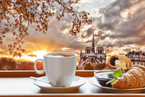 Обои Кружка кофе на блюдце рядом с тарелкой круассанов на фоне Нотр-Дама, Париж