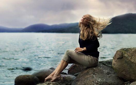 Обои Девушка с закрытыми глазами, с поднятой головой вверх, сидит на камне, на фоне морского пейзажа