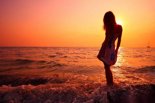Обои Девушка стоит в воде на фоне заката