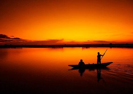 Обои Лодка с рыбаками в море на фоне заката