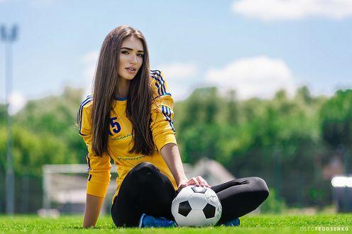 Обои Модель Настя в футбольной форме сидит на траве с мячом. Фотограф Олег Федосенко