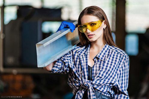 Обои Модель Елена в защитных очках, в клетчатой рубашке, завязанной узлом, держит на плече металлический профиль. Фотограф Олег Федосенко