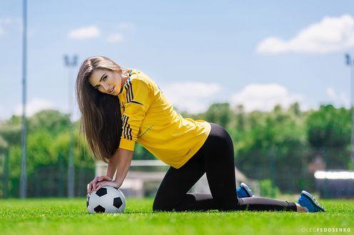 Обои Модель Настя в футбольной форме стоит на коленях на траве, руки положив на мяч. Фотограф Олег Федосенко