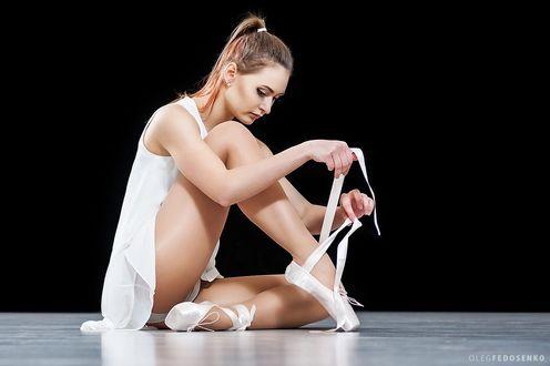 Обои Модель Екатерина в белом сидит на полу, завязывая пуанты. Фотограф Олег Федосенко