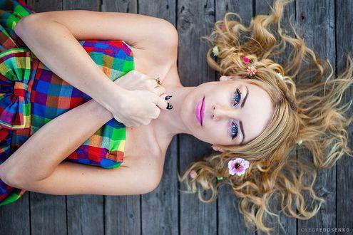 Обои Светловолосая модель Дарья с цветами на волосах, в разноцветном платье в клеточку лежит на деревянной поверхности. Фотограф Олег Федосенко