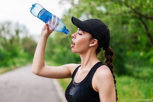 Обои Модель Анастасия с косой, в бейсболке, в черной майке, с закрытыми глазами пьет воду из бутылки. Фотограф Олег Федосенко