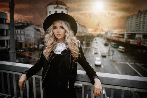 Обои Девушка-блондинка в шляпе стоит на фоне города, фотограф Sergey Piltnik