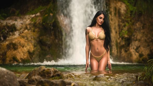 Обои Девушка в купальнике стоит в воде на фоне водопада