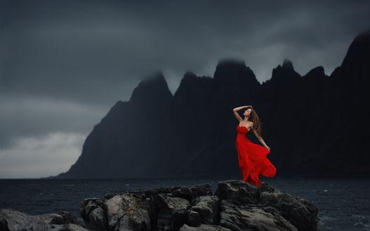 Обои Девушка в красном платье на фоне черных скал, надвигающихся туч и тумана, by baravavrova
