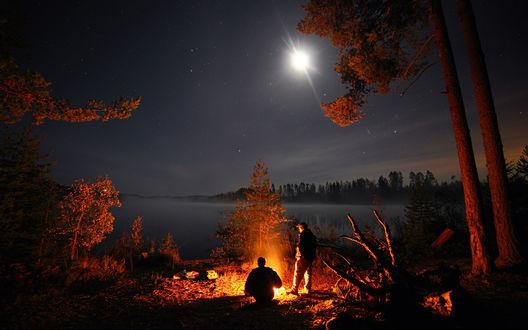 Обои Двое мужчин возле горящего костра на фоне ночного неба, озера и освещенных деревьев